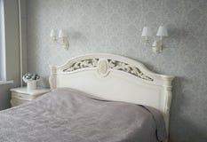 Säng med den sned huvudgaveln i sovrummet Inre i ljus signal Arkivfoton