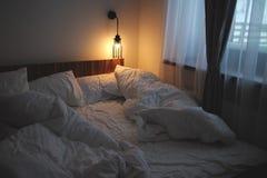 Säng med den vit ark, lampan och hemtrevlighet royaltyfria foton