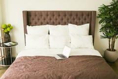 Säng med kuddar med nattduksbordet i sovrum fotografering för bildbyråer