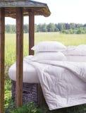 Säng med sänglinne i naturen Snövit säng mot en härlig natursikt royaltyfria foton
