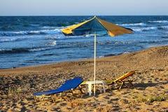 sängar för för Guling-blått strandparaply och sol med tabellen på en sandig strand vid havet Arkivfoton