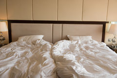 Sängar i ett hotellrum med det uppvecklade täcket arkivbilder