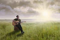 Sänger, der draußen Gitarre spielt Stockbilder