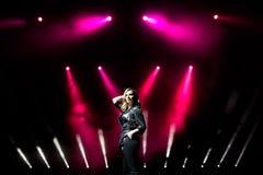 S?nger der jungen Frau mit bunten Lichtern auf Konzert lizenzfreies stockfoto