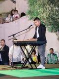 Sänger führt ein Lied durch und begleitet sich auf einem Tastatur instr Stockfoto
