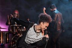 Sängerin mit dem Mikrofon und Rock-and-Roll-Band, die Hardrockmusik durchführen lizenzfreie stockfotos