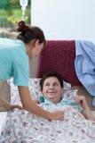 Sängliggande kvinna och hjälpsam sjuksköterska royaltyfri fotografi