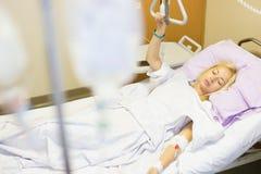 Sängliggande kvinnlig patient som återställer efter kirurgi i sjukhusomsorg Royaltyfri Bild
