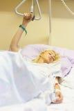 Sängliggande kvinnlig patient som återställer efter kirurgi i sjukhusomsorg Arkivbilder