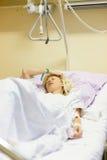 Sängliggande kvinnlig patient som återställer efter kirurgi i sjukhusomsorg Arkivbild