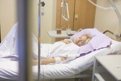 Sängliggande kvinnlig patient som återställer efter kirurgi i sjukhusomsorg Royaltyfri Fotografi