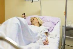 Sängliggande kvinnlig patient som återställer efter kirurgi i sjukhusomsorg Royaltyfri Foto