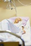 Sängliggande kvinnlig patient som återställer efter kirurgi i sjukhusomsorg Fotografering för Bildbyråer