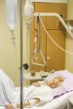 Sängliggande kvinnlig patient som återställer efter kirurgi i sjukhusomsorg Royaltyfria Bilder