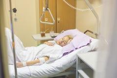 Sängliggande kvinnlig patient som återställer efter kirurgi i sjukhusomsorg Arkivfoto