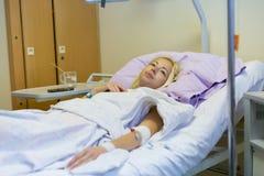Sängliggande kvinnlig patient som återställer efter kirurgi i sjukhusomsorg Royaltyfria Foton