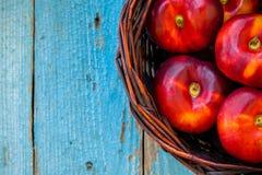 Sänker nya organiska nektariner för nya organiska plana nektariner i en korg Arkivfoton