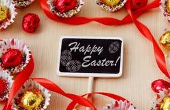 Säsonggarnering: svart tavla med inskriften lyckliga easter i ram för chokladägg på wood bakgrund Arkivfoton