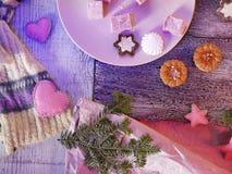 Säsongsbetonad dekorativ stilleben av den söta efterrätten, julbollar och filtleksaker på en trätextural bakgrund fotografering för bildbyråer