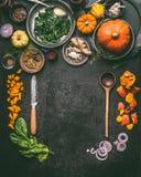Säsongsbetonad mat för höst som äter och lagar mat bakgrund med pumpa Mörkt lantligt köksbord med hjälpmedel arkivbild