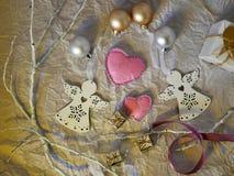 Säsongsbetonad sammansättning från dekoren av ett par av klädde med filt handgjorda hjärtor, två vita ängeljulpynt royaltyfri foto