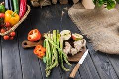 Säsongsbetonade grönsaker och halverat äpple på träbakgrund för tabellöverkant royaltyfria foton