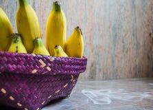 Sätt bananen inom den purpurfärgade korgen som vävas från förlade vasser på Arkivbilder