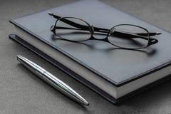 Sätt exponeringsglasen och skriva på en anteckningsbok Fotografering för Bildbyråer