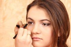 Sätt skönhetsmedel till ung flickasminkögonen Arkivbild