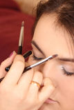 Sätt skönhetsmedel till ung flickasminkögonen Arkivfoto