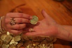 Sätta det guld- myntet in i gömma i handflatan Arkivfoton