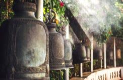 Sätta en klocka på i buddistiskt tempel Arkivfoto