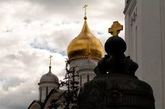 Sätta en klocka på och templet med guld- kupoler på bakgrunden av molnen Arkivfoto