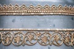 Sätta en klocka på specificerar in: belägga med metall den guld- prydnaden. Royaltyfri Foto