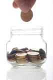 Sätta ett mynt in i glasflaskan Fotografering för Bildbyråer