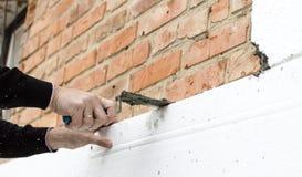 Sätta lim på polystyren på tegelstenväggen royaltyfria bilder