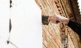 Sätta lim på polystyren på tegelstenväggen royaltyfri bild