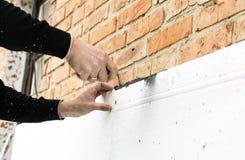 Sätta lim på polystyren på tegelstenväggen arkivbilder