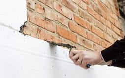 Sätta lim på polystyren på tegelstenväggen royaltyfri foto