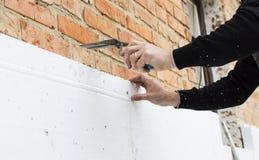 Sätta lim på polystyren på tegelstenväggen arkivfoton