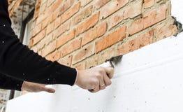 Sätta lim på polystyren på tegelstenväggen royaltyfri fotografi