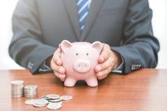 Sätta mynt in i piggy bank-begrepp av besparingar royaltyfria bilder