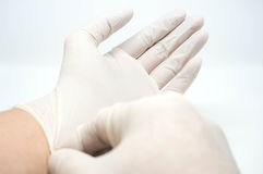 Sätta på disponibla sterila vita handskar på vit bakgrund Royaltyfria Bilder