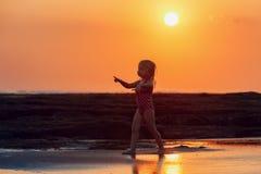 sätta på land barn för white för semestern för sanden för familj fyra tropiskt Det lyckliga barnet går på solnedgångstranden Arkivfoto