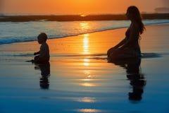 sätta på land barn för white för semestern för sanden för familj fyra tropiskt Moder med barnet på solnedgångstranden Arkivfoto