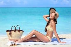 Sätta på land bikinikvinnasolen som garvar på sommarsemester Arkivfoto