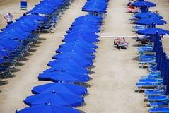 sätta på land blåa paraplyer Royaltyfri Fotografi