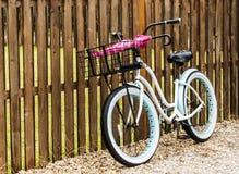 Sätta på land cykeln som parkeras mot ett staket med paraplyer i dess korg Royaltyfri Foto