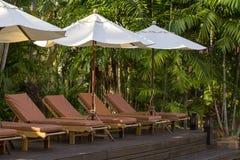 Sätta på land dagdrivare och paraplyer på stranden bredvid havet i det tropiska hotellet, Thailand Arkivfoto