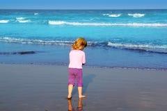 sätta på land den blonda flickan little bakre havsturkossikt Arkivfoto
